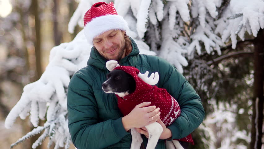 A young man in a santa hat is holding his dog in his arms. A pet in a Christmas costume. Christmas holidays in the forest