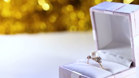 Gold Pearl Rings in the White Gift Box With Gold Glitter Texture On Background.