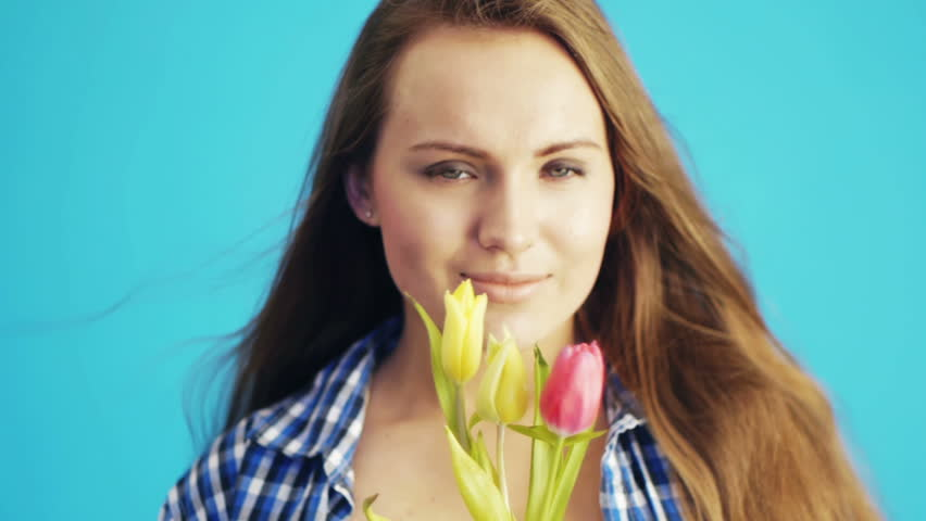 Young woman sniffing tulips at studio | Shutterstock HD Video #3453704