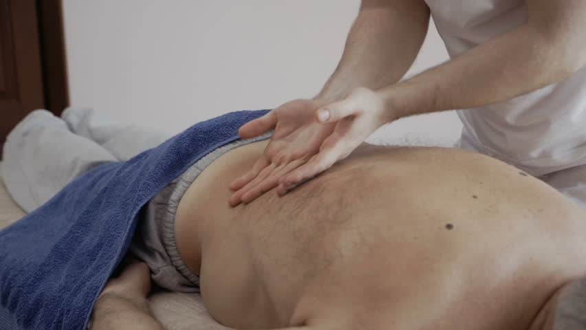 Masseur professionally massages back of old man | Shutterstock HD Video #34554184