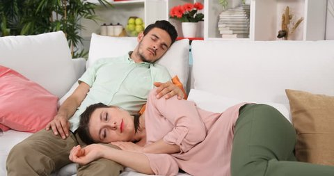 Tired Young Couple Sleeping Together on Modern Sofa in Living Room Exhausted Day