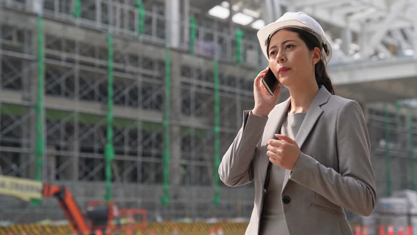 successful Confident woman business architect in hardhat holding talking on the mobile phone while standing outdoors and against building the structure.