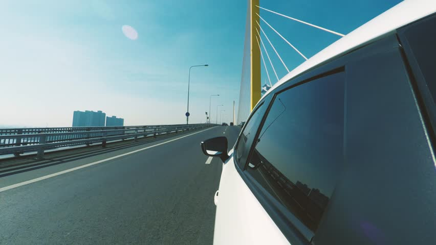 4K - Shot of car moving through the Bhumibol bridge on a clear blue day. Camera placed on upper left side of the vehicle and faces forward. (POV #10) | Shutterstock HD Video #34615324
