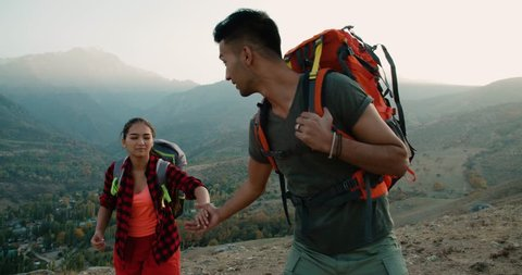 a couple of Asian hikers in the mountains, the boyfriend helps the girl holding her hand