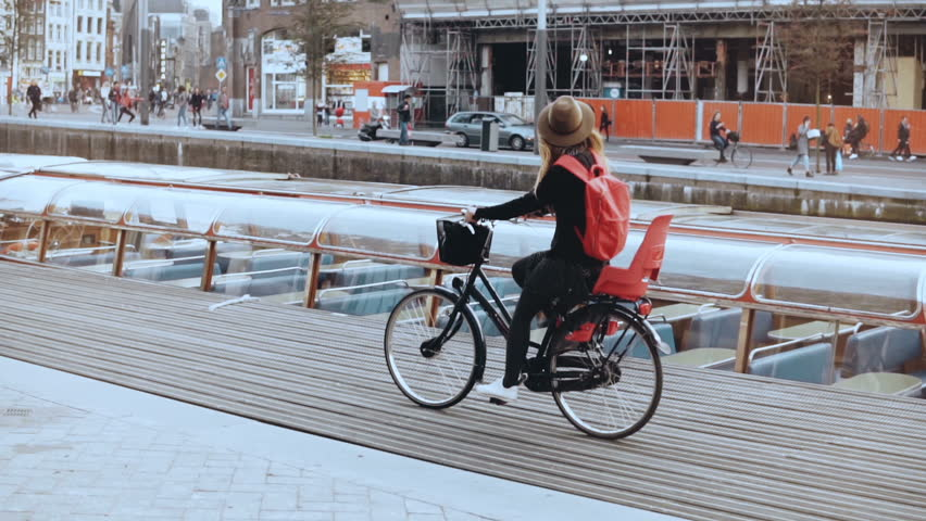 Cute European girl rides bicycle along river quay. Touristwoman in hat on a city bike in Amsterdam. Real time side view.