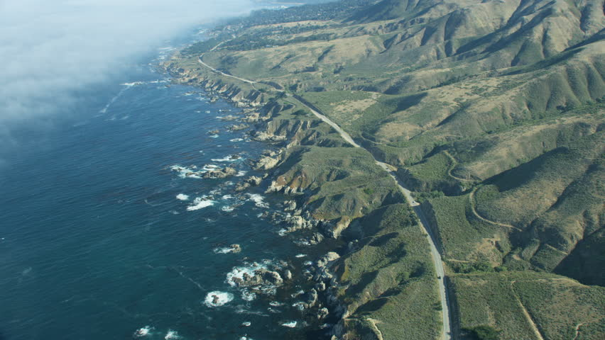 Aerial view coastal mountain ranges Big Sur rocky coastline offshore fog vehicles travelling along Cabrillo Highway California USA RED WEAPON