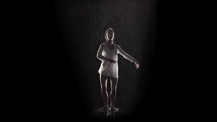 woman dancing and rotating under the rain with black background and backlight
