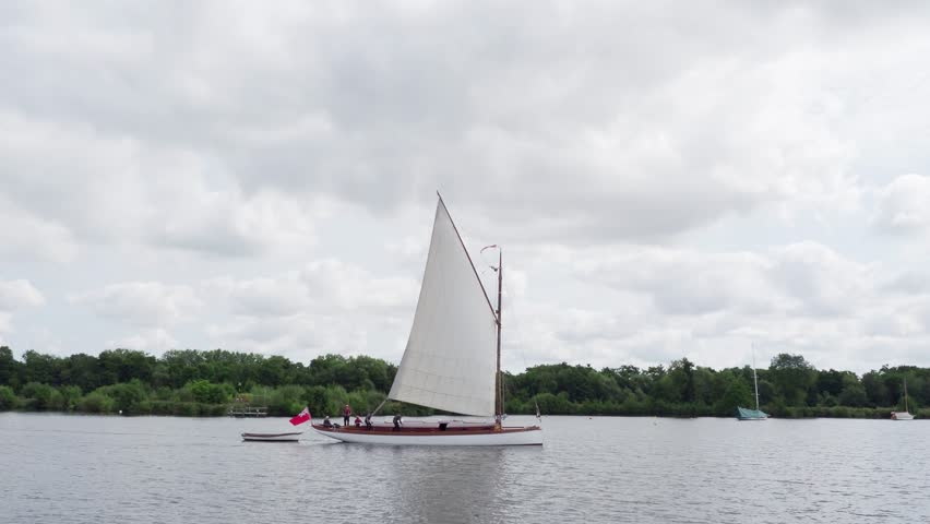 Wroxham, Norfolk - 21st August 2017: On a dull, cloudy day one of the last Norfolk Wherry yachts named 'White Moth' sails across the rippled waters of Wroxham Broad.