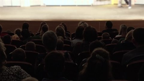 People, parents, children at the cinema or at the theatre during the performance. A theater stage
