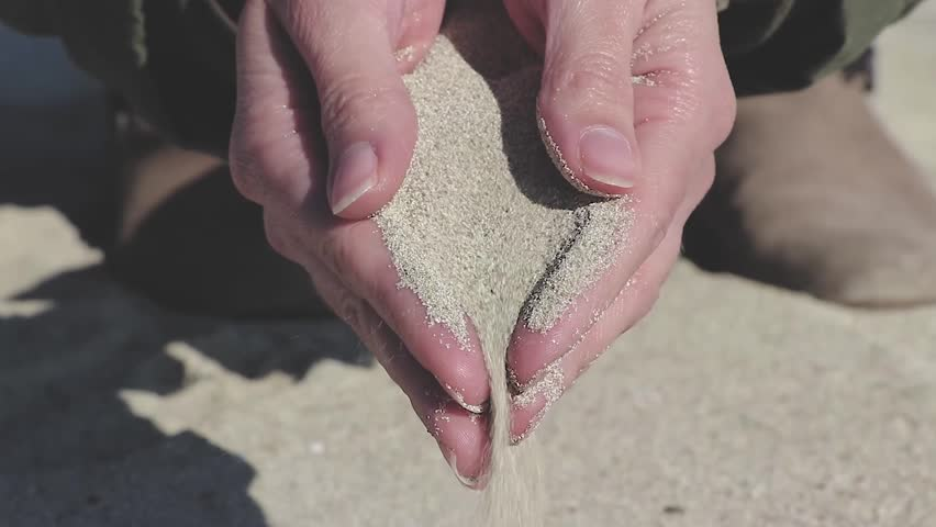 woman holding fine sand in hands and slow release #34736584