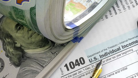 USA tax form 1040 and dollar bills, close up. High angle view.