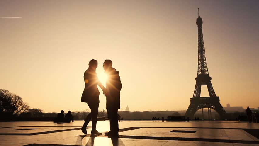 happy affectionate couple in Paris near Eiffel tower, silhouettes of man and woman on honeymoon in Europe