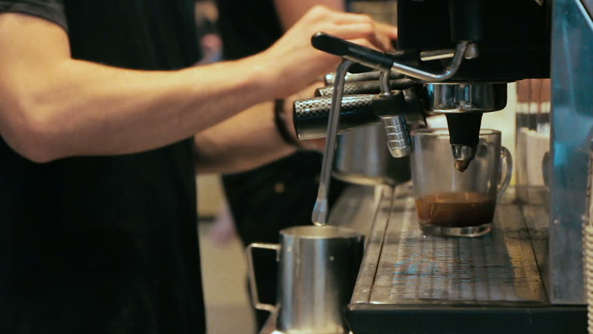 Barista making coffee in coffee machine at a busy coffee shop
