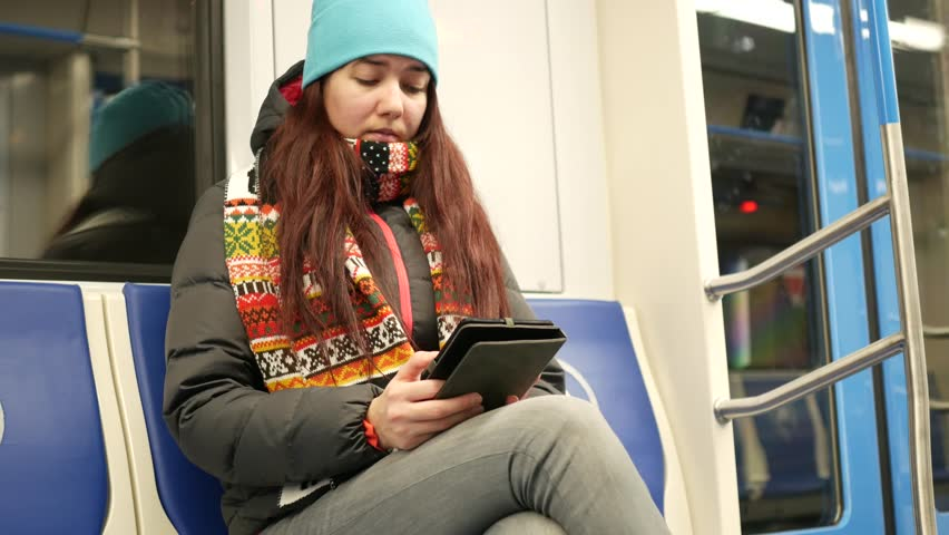 Young woman read e-book in subway train at metro