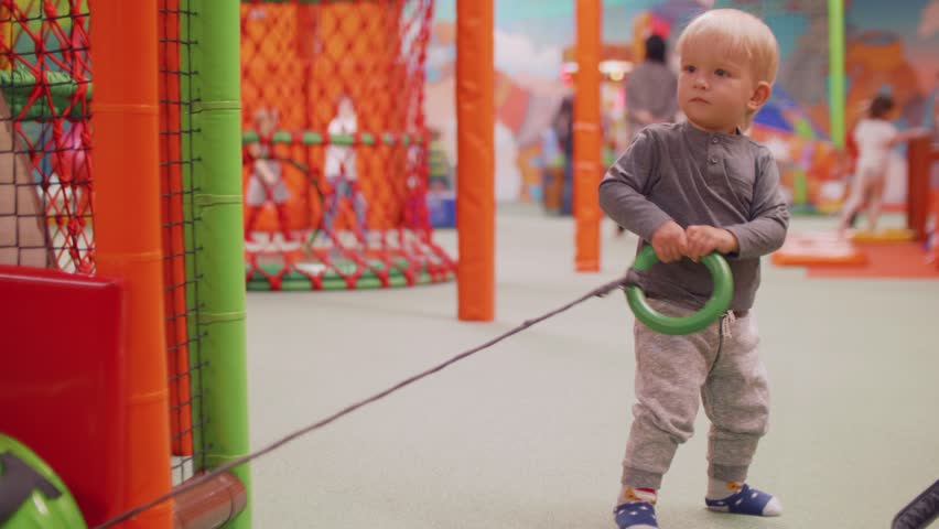 Blond toddler doesn't manage to dag tube and walks away