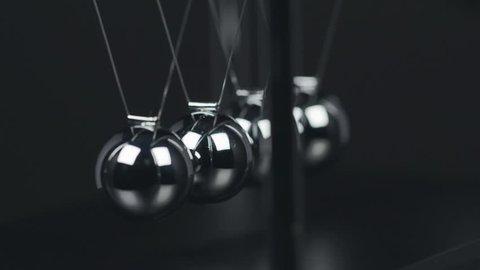 Slow motion shot of a Newton's Cradle.