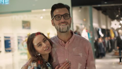 Young couple in shopping mall pausing to look at window display feel happy smiling talking shopper lockdown interior christmas love girl man together close up portrait slow motion