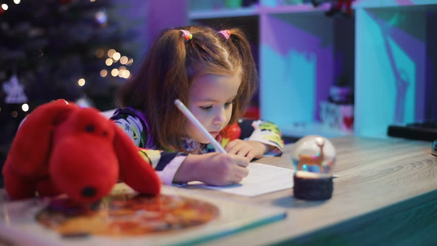 Little pretty girl with two pigtails sitting at table. Stuffed animal lying on table. Little lady writing letter for Santa Claus.