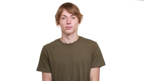 Skinny man in green t-shirt throwing up hands expressing innocence saying oops not know what's going on over white background. Concept of emotions
