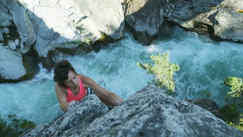 Active Caucasian American roped female climber rock climbing above white water canyon river outdoors in Squamish Valley Canada RED WEAPON
