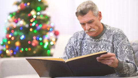 The crying pensioner watch an photo album near the christmas tree