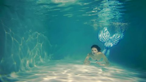 a woman swims in the pool, a lady dives under the water with a fish tail, she swims into the depths