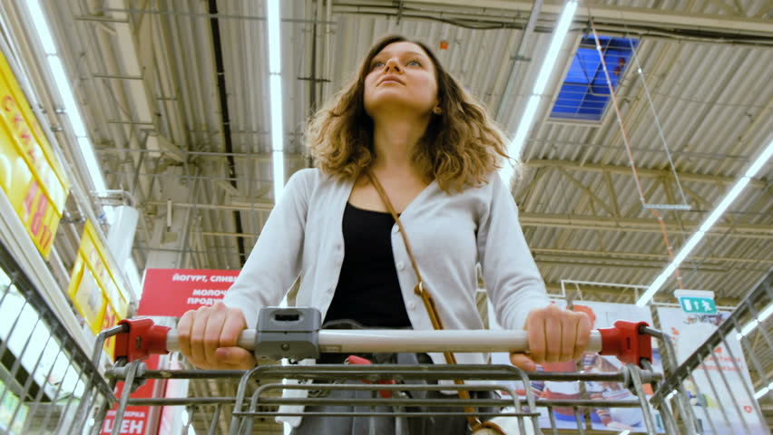 A woman walks with a cart and selects yogurt, puts in a basket in the supermarket, 4K. | Shutterstock HD Video #34842769
