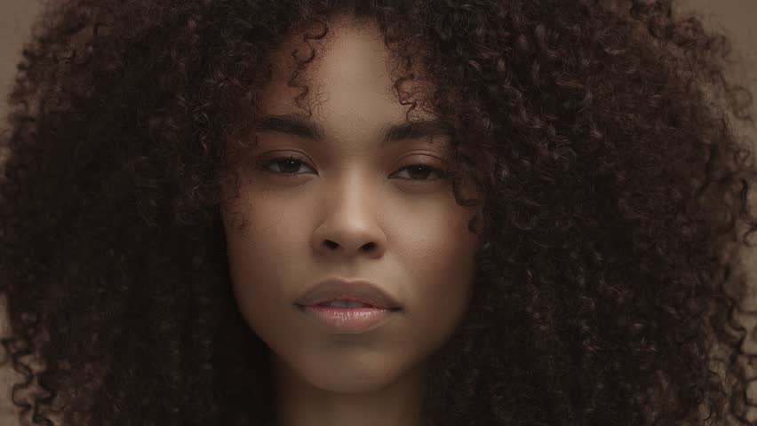 front portrait of black woman with huge curly hair looking at camera. ideal skin concept. Beige tones natural makeup