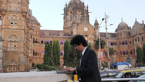 4K footage of office going young man using mobile phone, tablet in front of CST previously Victoria Terminus.