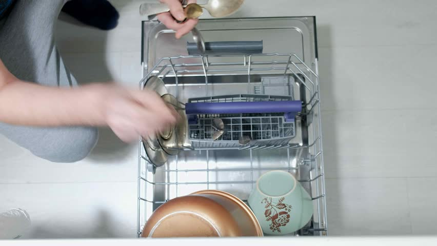 A man puts dirty dishes in the dishwasher 4k