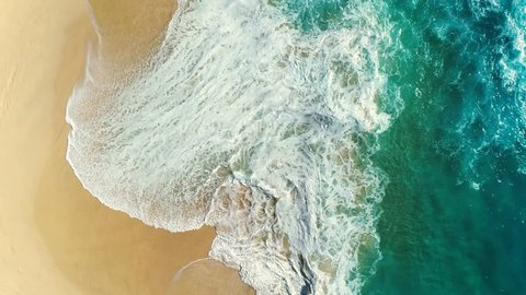 Aerial view waves break on white sand beach. Sea waves on the beautiful beach aerial view drone 4k shot.