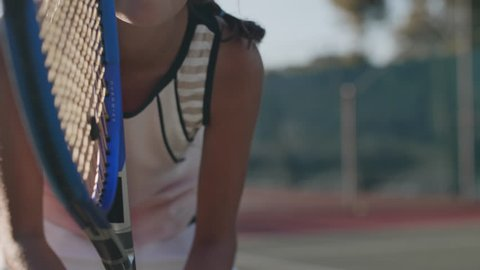 Close up portrait of young female tennis player concentrating and focusing on her game