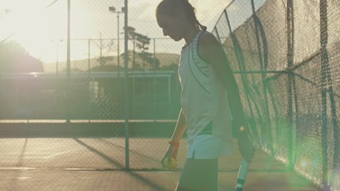 Fit healthy sporty teenager playing tennis, getting ready to serve on court slow motion with sun flare