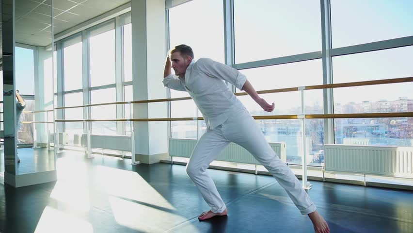 Dancer in white suit making vigorous movements at studio and showing big finger upwards. Jocund person has positive emotions. Concept of graduating dance school. | Shutterstock HD Video #34914424