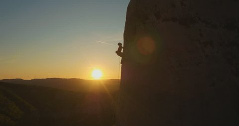 Aerial fly-by a man rock climbing outdoors at amazing sunset.