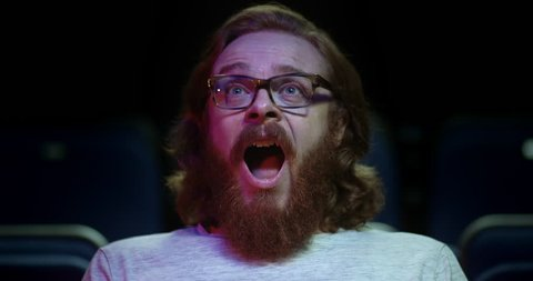 Mouth open and wide eyed - A man reacts in awe to a scene from a movie while at the movie theatre.