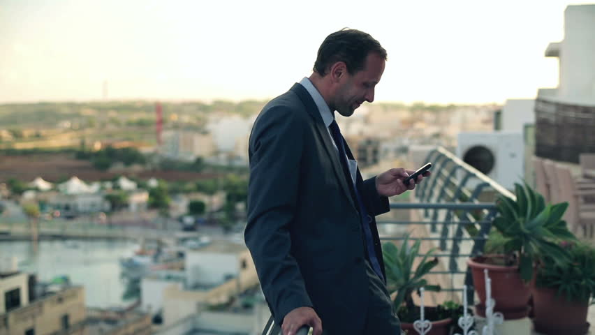 Business man standing on the terrace with cellphone, crane shot