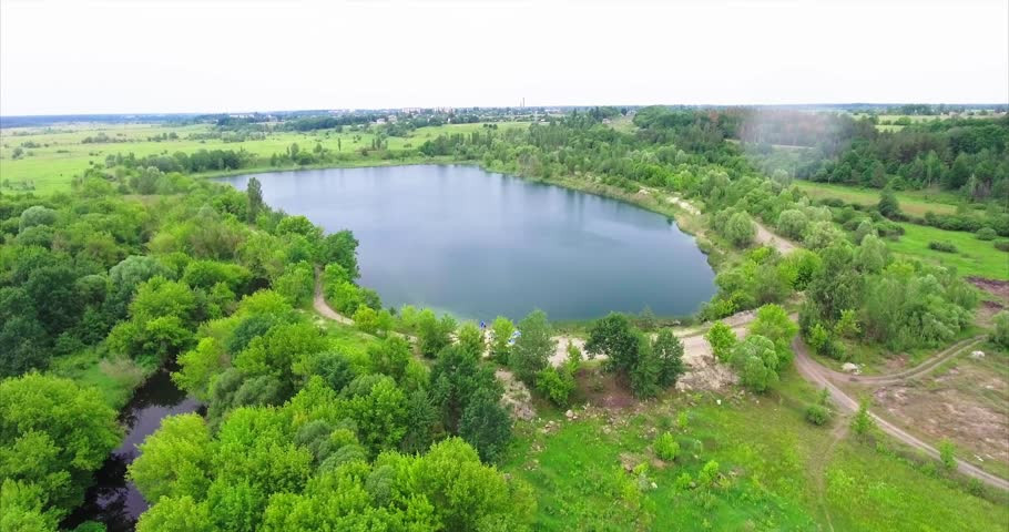 Aerial survey. Forest landscape with views to a small river. Blue lake with beautiful green trees. Summer cloudy day, forest landscape. A narrow river flows through the field.