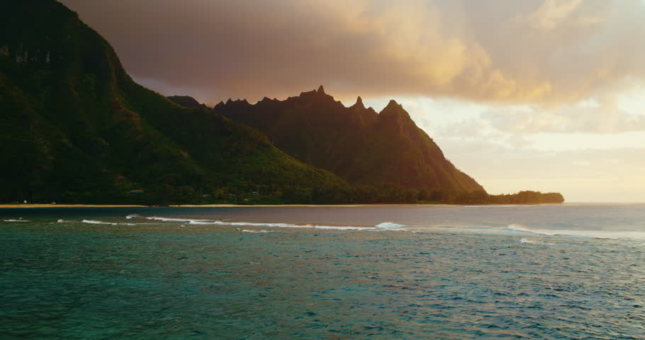 Cinematic aerial view of dramatic mountains and ocean waves on North Shore of Kauai at sunset