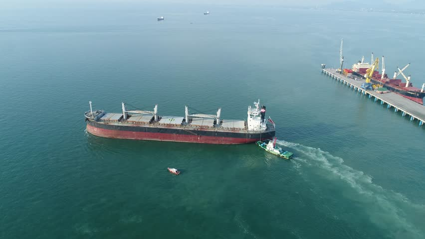 general bulk cargo ship under navigating by pilot leader takes the ship sailing safety circumstance from the wharf terminal seaport assist by tugs boat serving