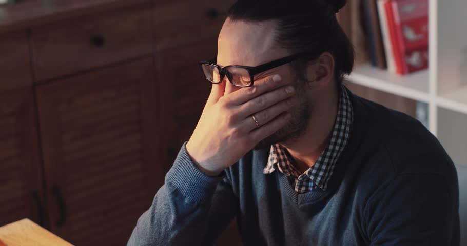 Tired of working on the computer young bearded man in a stylish look pushes up his glasses, rubs his eyes, takes deep breath. Workaholic, working hard, career ladder, making money. Close up view | Shutterstock HD Video #34954924