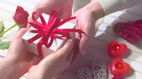 Valentine Gift. Young Couple Hands holding gift box over wooden background. St. Valentine's Day, Love concept. Top view, tabletop. Man giving gift, romance, dating concept, giving gift. Slow motion 4K
