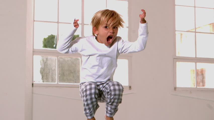 Boy in pajamas jumping and yelling in front of window in slow motion