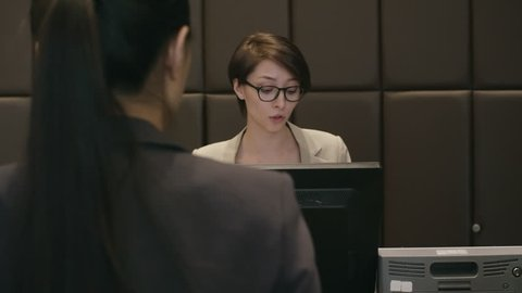 Female receptionist greeting guests and talking with them at check in desk in hotel while African businessman giving passport to her for registration
