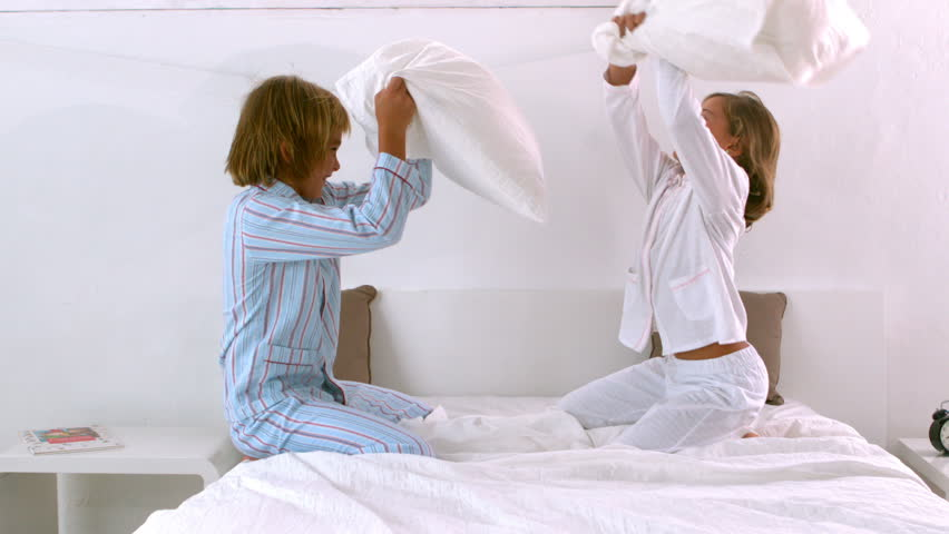 Siblings having a pillow fight on the bed in slow motion