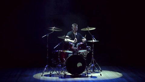 Male drummer playing drums on a black background, slow motion. A man playing drums at a concert or party. Empty stage and concert lighting with smoke.
