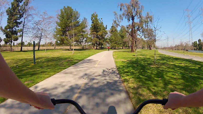 LONG BEACH, CA - February 23, 2013: The POV of someone riding a bicycle in El Dorado Regional Park circa 2013 in Long Beach.  Long Beach promotes bike riding and exercise.