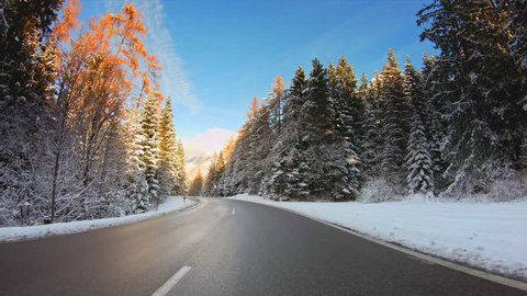POV vehicle drive across beautiful winter nature, forest evergreen trees with snow, mountains, asphalt road and sunny blue sky, car travel gopro point of view