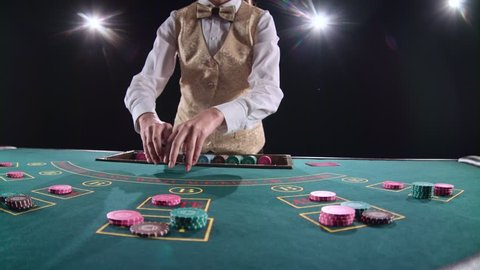 Casino croupier distributes cards on the poker table top using cut card. Black background. Bright light. Slow motion