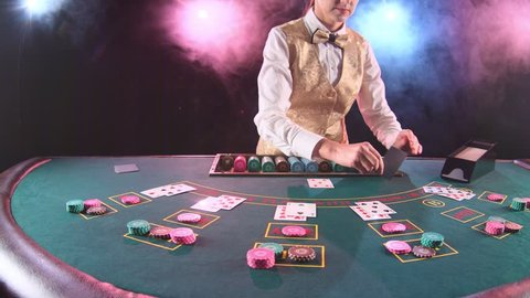 Casino stickman woman in gold vest takes the cards from card holder at the game table. Black background. Smoke. Slow motion